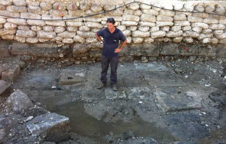A member of the Marine Archaeology Unit of the Israel Antiquities Authority standing on the ancient quay that was exposed in Akko. In the middle of the picture one can see the floor of the quay, built of large dressed stones. In some of the stones there is a hole for inserting a wooden pole – probably for mooring and/or dragging the boat.